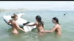 Three crazy slender teenagers are posing naked on the public beach