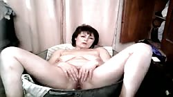 Hot black-haired mature chick is revealing her pussy in the bedroom