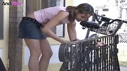 Andi Pink is riding on a bike and then slowly starting to undress